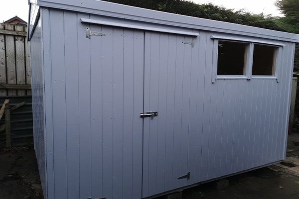 An image of a light blue shed with a window and double doors.
