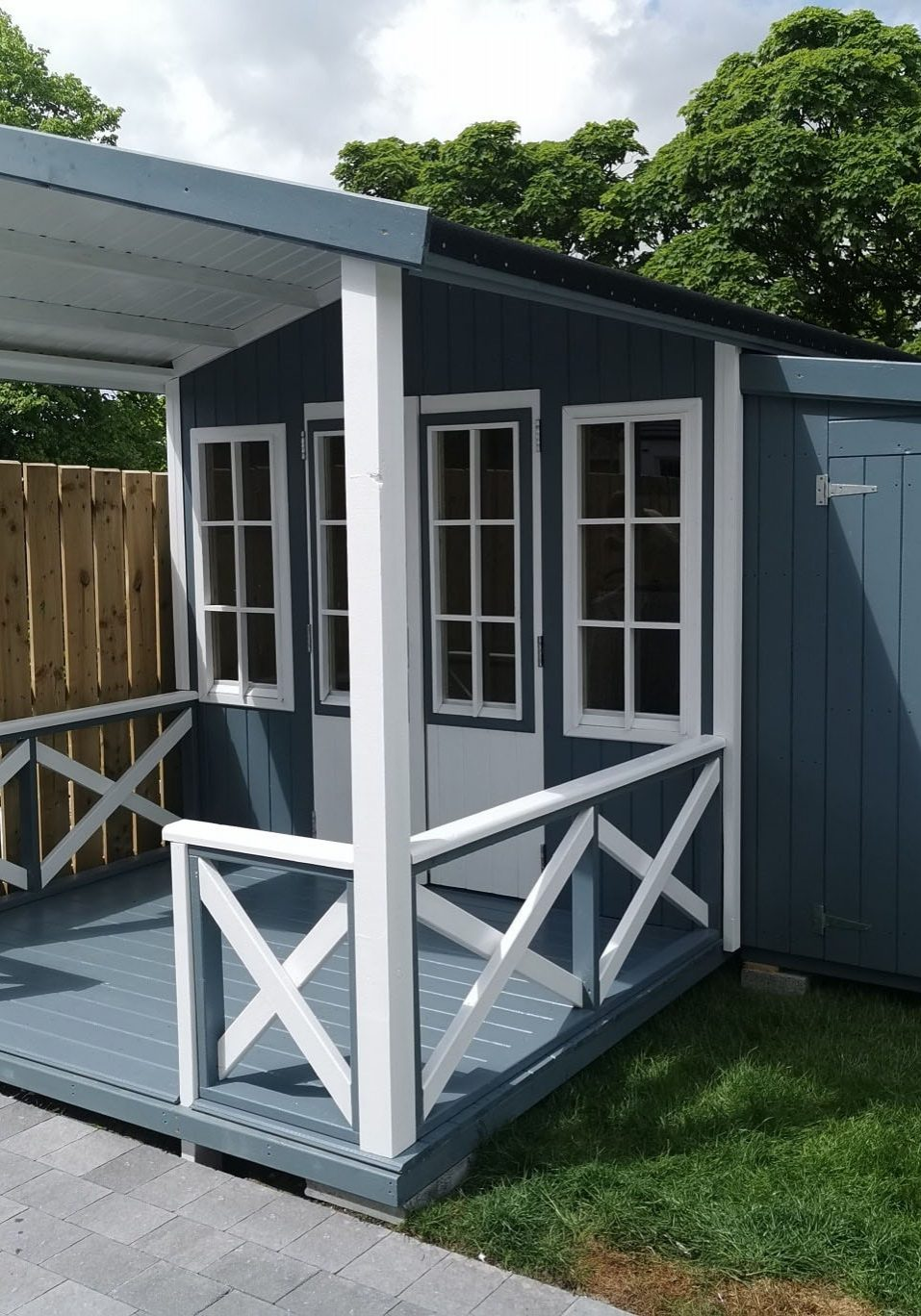 An image of a blue grey garden shed with a patio and French doors.